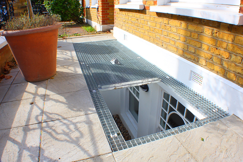 A removable grate provides this basement conversion with natural light and emergency access