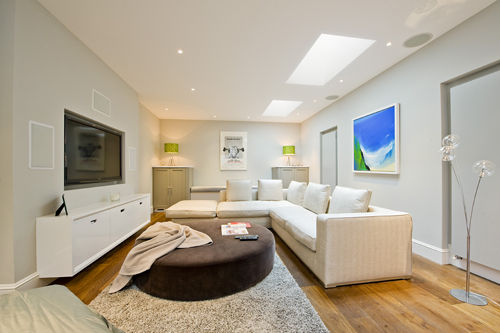 An airy basement with seating, television and skylights
