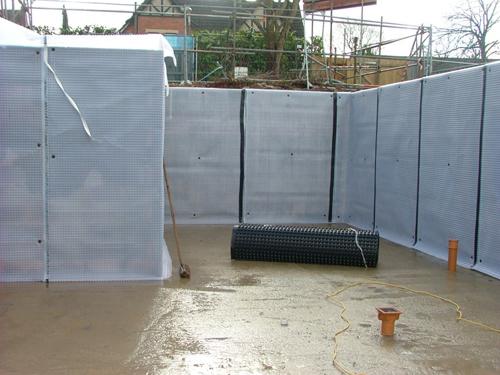 Contractors applying waterproofing measures to a basement construction