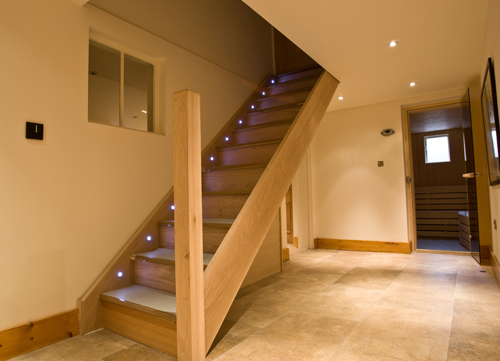 An LED-lit wooden staircase leading to a basement conversion