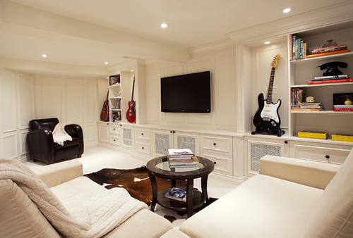 A basement conversion with seating, television and guitars