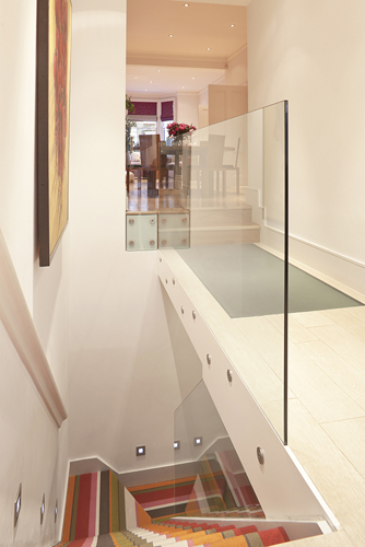 A staircase with sheet glass balustrade leading to a converted basement